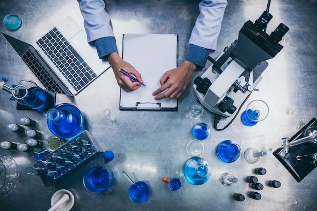 Draufsicht arbeitsbereich im labor mit mikroskop, laptop und laborwerkzeugen