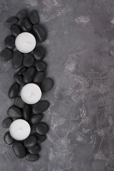 Draufsicht aromatherapie steine mit kerzen auf dem tisch