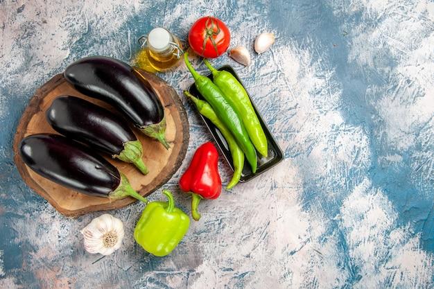 Draufsicht auberginen auf baumholzbrett peperoni auf schwarzem teller