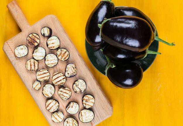 Draufsicht auberginen und auberginenscheiben auf teller und schneidebrett auf gelbem hintergrund. horizontal