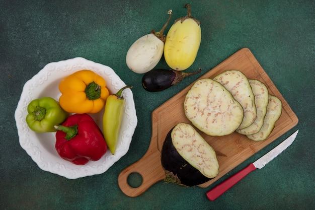 Draufsicht auberginenscheiben auf einem schneidebrett mit einem messer mit paprika auf einem teller auf grünem hintergrund