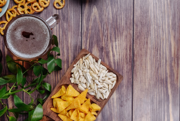 Draufsicht auf abwechslungsreiche biersnacks, sonnenblumenkernchips und mini-brezeln mit einem krug bier auf rustikal mit kopierraum