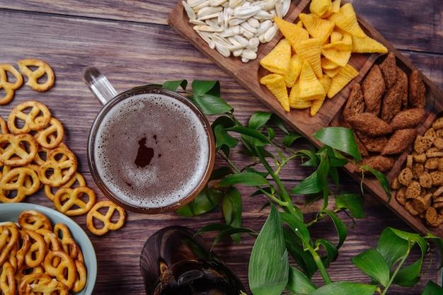 Draufsicht auf abwechslungsreiche biersnacks, sonnenblumenkerne, chips, brotcracker und mini-brezeln mit einem becher bier auf rustikal