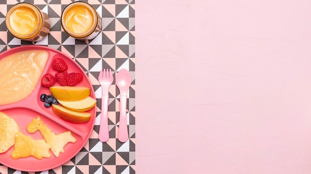 Draufsicht auf äpfel und himbeeren mit babynahrung