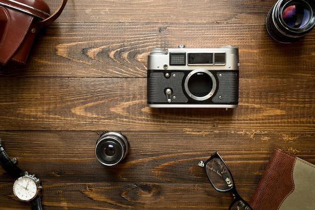 Draufsicht auf alte analoge kamera, objektive, notebook und uhren