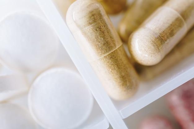 Draufsicht auf alternative organische medizin oder pflanzliche viatmin-ergänzungskapsel-tablette auf pillenfallhintergrund. konzept der gesunden ernährung.