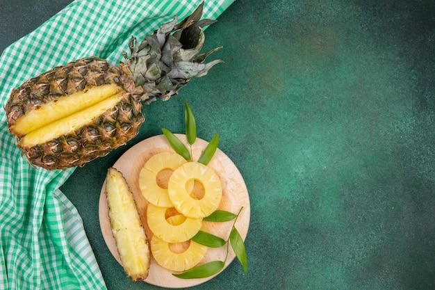 Draufsicht auf ananas mit einem stück aus ganzen früchten und ananasscheiben auf schneidebrett auf kariertem stoff und grüner oberfläche ausgeschnitten