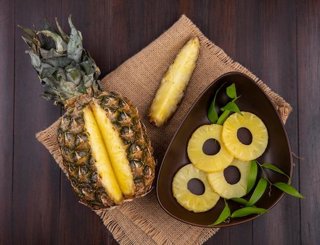 Draufsicht auf ananas mit einem stück aus ganzen früchten und einer schüssel ananasscheiben auf sackleinen und holzoberfläche