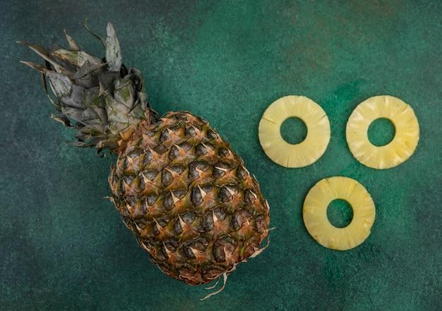 Draufsicht auf ananas und ananasscheiben auf grüner oberfläche