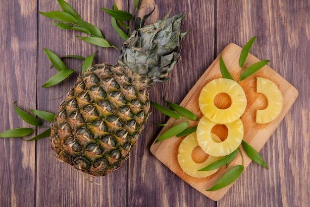 Draufsicht auf ananas und ananasscheiben mit blättern auf schneidebrett und holzoberfläche