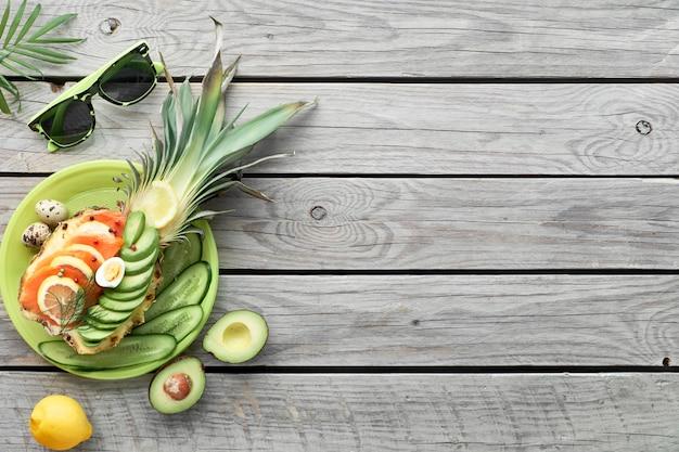 Draufsicht auf ananasboote mit geräucherten lachs- und avocadoscheiben mit zitronen- und wachteleiern, flach auf altem holztisch liegend
