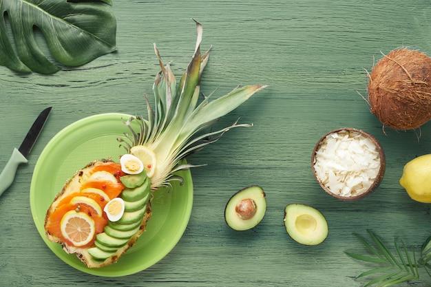 Draufsicht auf ananasboote mit geräucherten lachs- und avocadoscheiben mit zitronen- und wachteleiern