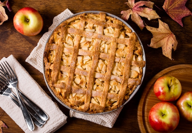 Draufsicht auf apfelkuchen zum erntedankfest mit besteck und blättern