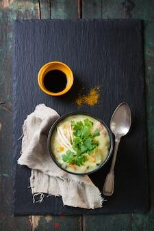 Draufsicht auf appetitliche suppe mit neben einem löffel