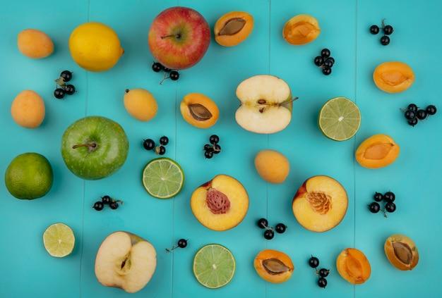 Draufsicht auf aprikosen mit äpfeln, zitrone, schwarzen johannisbeeren und limettenscheiben auf einer hellblauen oberfläche