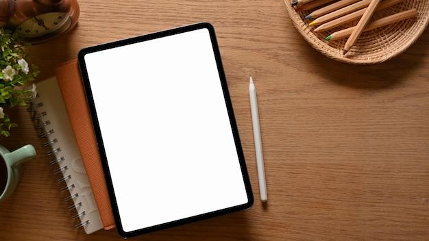 Draufsicht auf arbeitsbereich mit buntstiften digitaler tablet-notizbücher