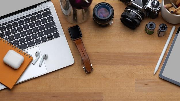Draufsicht auf arbeitsbereich mit digitalen geräten, kamera, zubehör und kopierraum auf holztisch