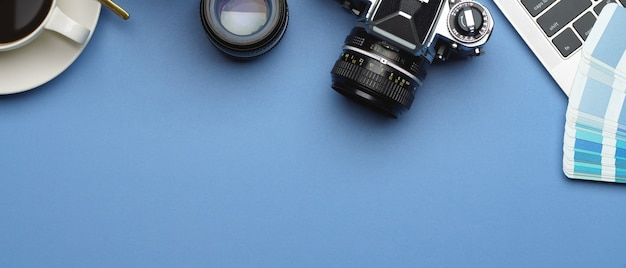 Draufsicht auf arbeitsbereich mit kamera, laptop, objektiv, tasse und kopierraum im arbeitszimmer zu hause