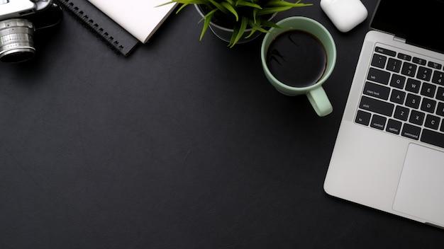 Draufsicht auf arbeitsbereich mit laptop, kaffeetasse, notizbüchern und kopierraum