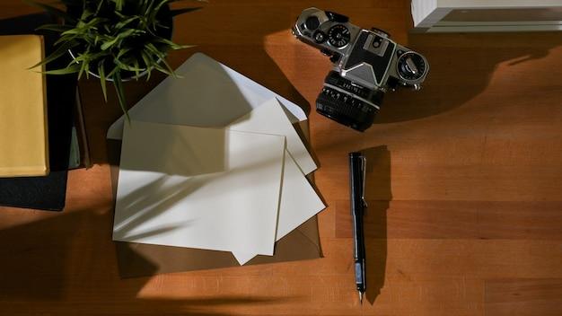 Draufsicht auf arbeitsbereich mit modellkarten, kamera, briefpapier, büchern und kopierraum im arbeitszimmer zu hause