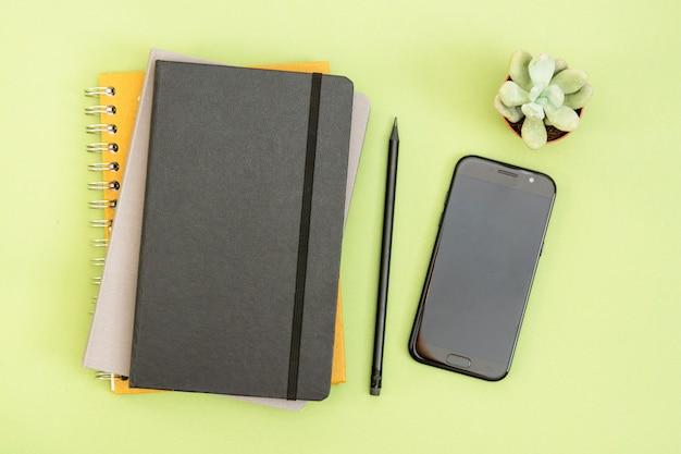 Draufsicht auf arbeitstisch. schwarzes geschlossenes notizbuch, kaffeetasse und smartphone. kopieren sie platz für text. design mock up.