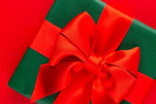Draufsicht auf arrangierte verpackte weihnachtsgeschenkboxen mit bändern auf roter tischplatte