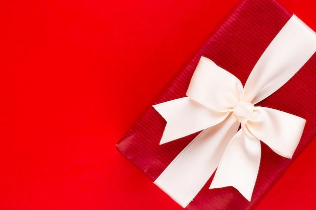 Draufsicht auf arrangierte verpackte weihnachtsgeschenkboxen mit bändern auf roter tischplatte.