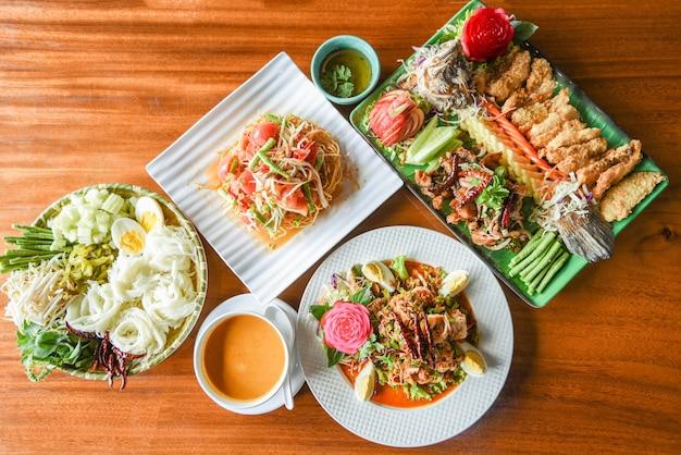 Draufsicht auf asiatisches thailändisches essen mit curry-papayasalat mit thailändischen reisnudeln, garnelensalat und fischfischsalat, serviert auf tischplatte aus holz