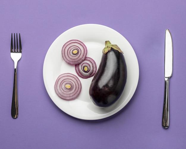 Draufsicht auf aubergine und zwiebel auf teller mit besteck