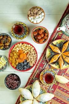Draufsicht auf azerbaijani pakhlava serviert mit nüssen getrockneten früchten rosinen und tee