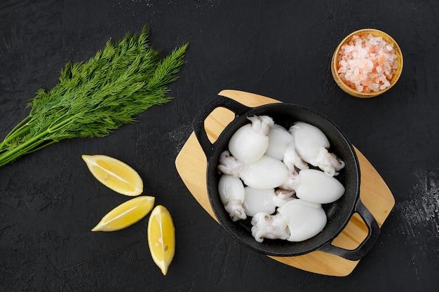 Draufsicht auf baby-tintenfisch in gusseiserner pfanne mit dill, salz und zitrone