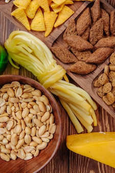 Draufsicht auf bier salzige snacks maiskolben brotcracker schnurkäse und gesalzene erdnüsse auf rustikalem holz