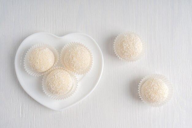 Draufsicht auf bio-kokos-trüffel, serviert in herzförmiger platte auf weißem holzhintergrund