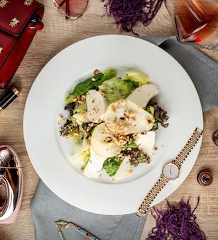 Draufsicht auf birnensalat mit salatkäse-kiwi und walnüssen