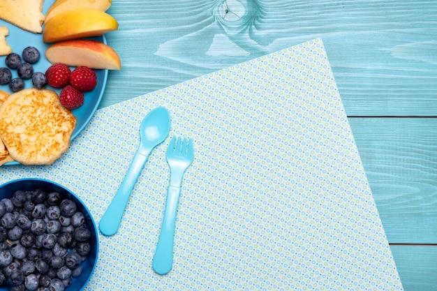 Draufsicht auf blaubeeren mit besteck und früchten