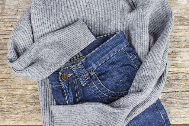 Draufsicht auf blaue jeans und graue strickjacke auf holzhintergrund. konzept für modische kleidung.