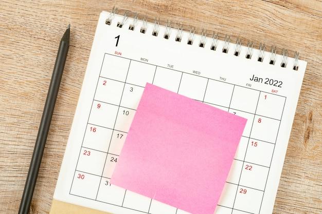 Draufsicht auf bleistift, kalenderplanung und frist mit haftnotiz auf holzhintergrund, kalendertisch 2022 im januar-monat