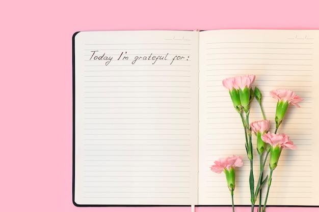 Draufsicht auf blumen auf offenem papiernotizbuch mit handgeschriebenen worten heute bin dankbar für dankbarkeit jo ...