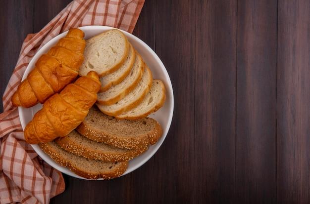 Draufsicht auf brote als geschnittenes baguette und croissants aus braunem maiskolben in platte auf kariertem stoff auf holzhintergrund mit kopierraum