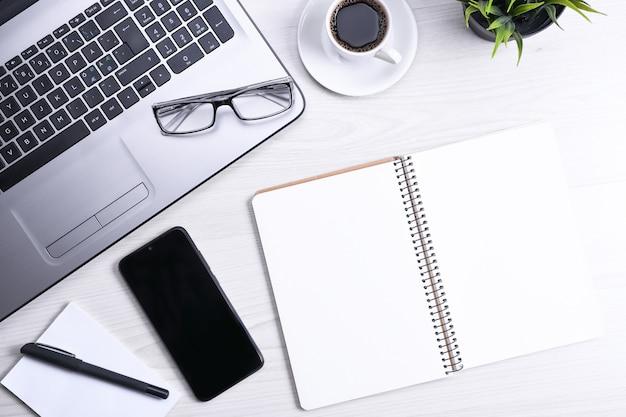 Draufsicht auf büroarbeitsplatz, schreibtisch aus holz mit laptop-notebook, tastatur, stift, brille, telefon, notizbuch und tasse kaffee.
