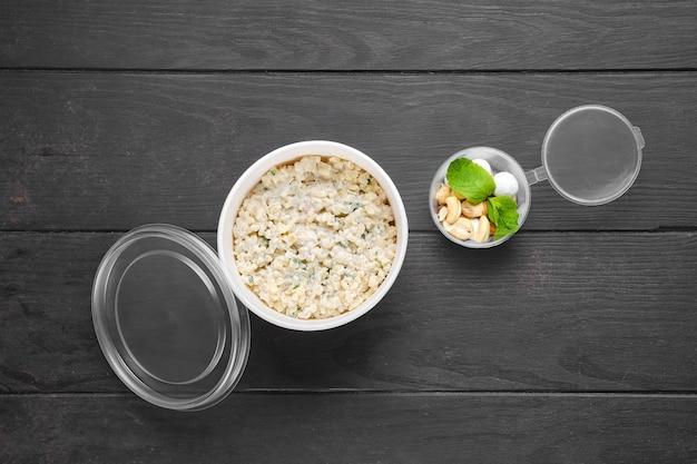 Draufsicht auf bulgur-porridge mit mandel- und haselnüssen und preiselbeeren in zuckerpulverpanade in take-away-verpackung