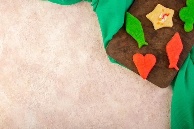 Draufsicht auf bunte köstliche kekse, die auf dem braunen holzschreibtisch und auf der rosa oberfläche unterschiedlich gebildet werden