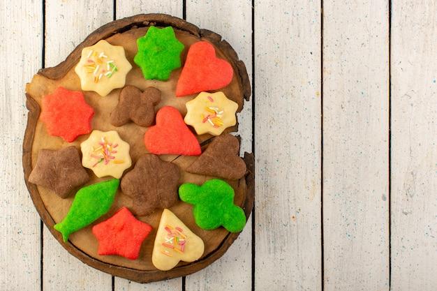 Draufsicht auf bunte köstliche kekse, die auf dem braunen schreibtisch und der grauen oberfläche unterschiedlich gebildet werden