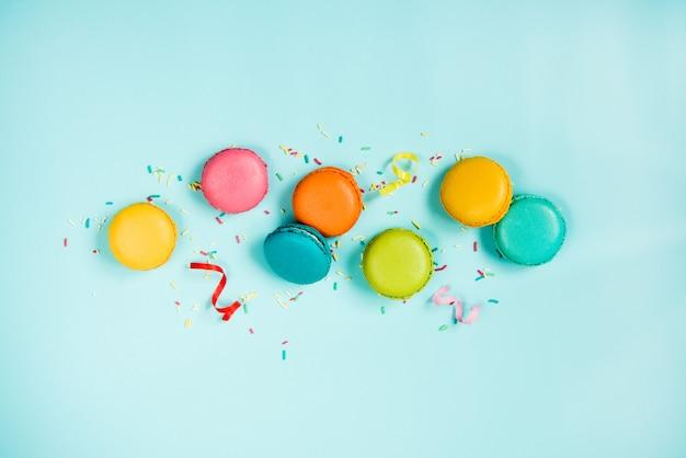 Draufsicht auf bunte makronen, zuckerstreusel und partybänder, die auf blau angeordnet sind