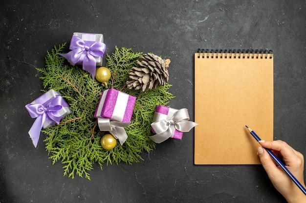Draufsicht auf bunte neujahrsgeschenke dekorationszubehör und nadelbaumkegel neben notebook auf dunklem hintergrund