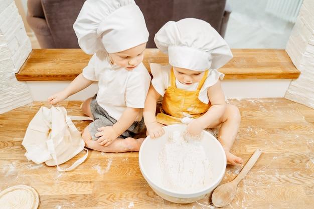 Draufsicht auf charmante neugierige kinder, bruder und schwester in einem anzug von köchen sitzen auf dem küchentisch und bereiten teig für pfannkuchen zu. das konzept, kindern das arbeiten und kochen beizubringen