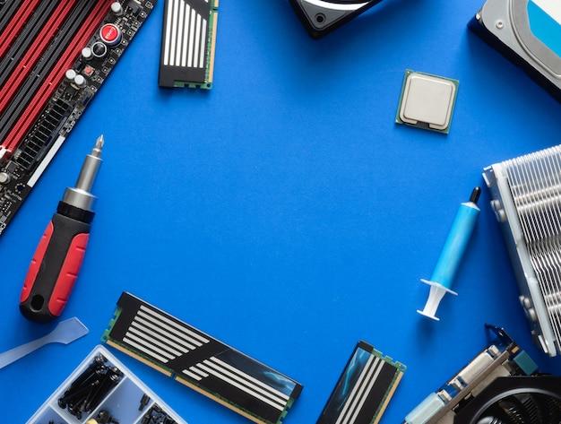 Draufsicht auf computerteile mit festplatte, ram, cpu, grafikkarte und hauptplatine auf blauem tabellenhintergrund.