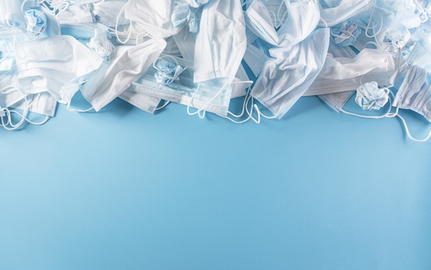 Draufsicht auf covid19-einwegmasken auf pastelnblauem hintergrund