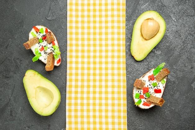 Draufsicht auf cremige avocados mit brot und pfeffer auf dunkelgrauer oberfläche