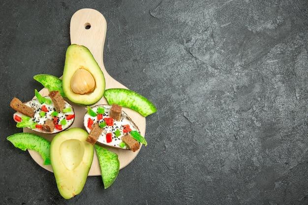Draufsicht auf cremige avocados mit brot und pfeffer und frischen avocados auf der grauen oberfläche